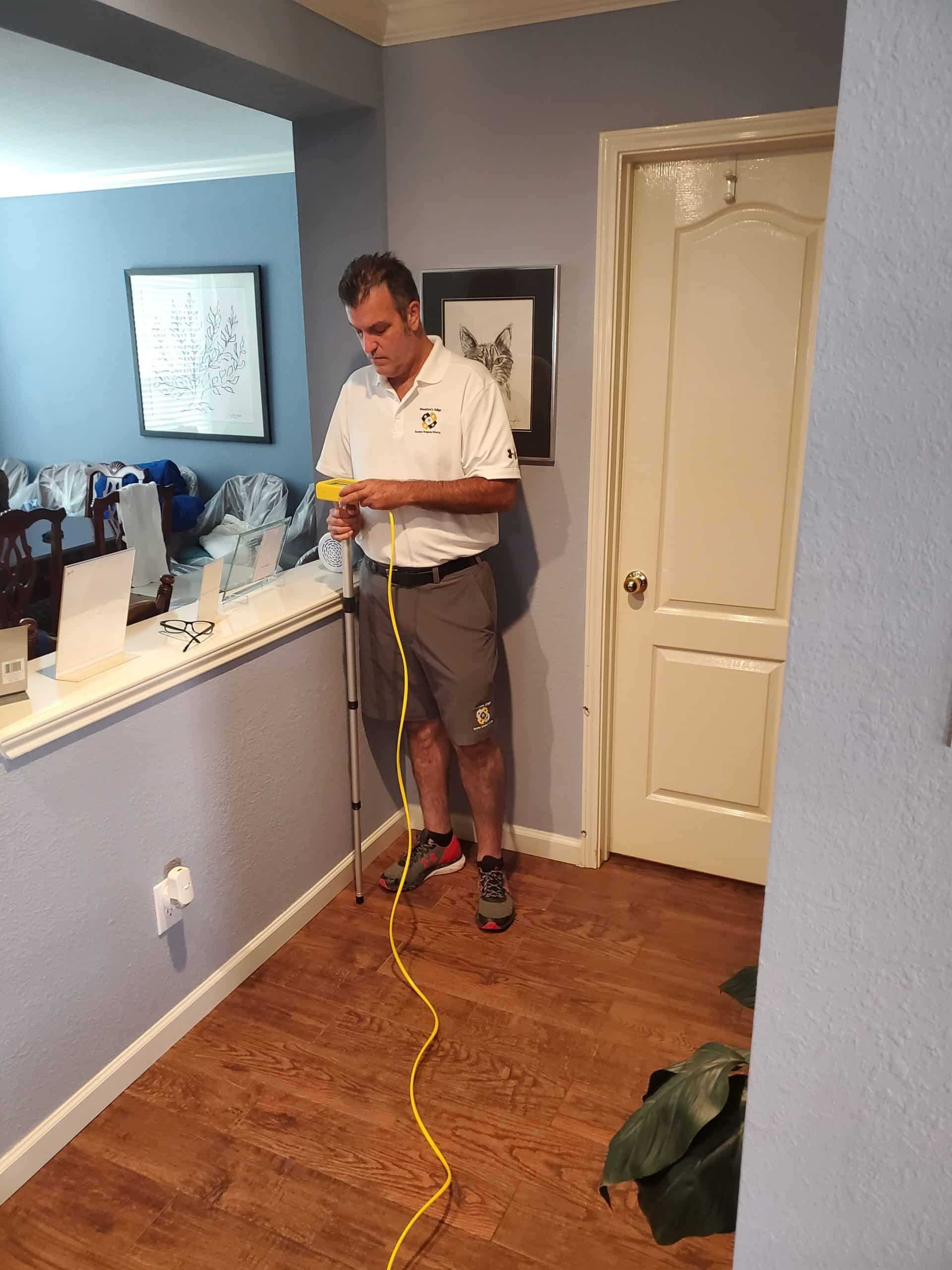 Photo of a home inspector performing zip level measurements in Magnolia Texas